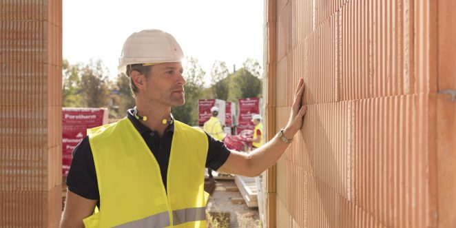 Builder on construction site touching clay block wall, construction workers and clay block pallets in the background