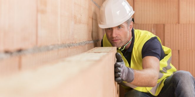 Construction worker checking alignment of mineral-wool filled clay block